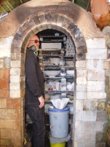 Peter inside brick kiln with shelves of pottery